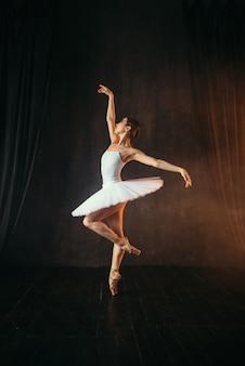 Bailarina de vestido branco e sapatilhas de ponta dançando