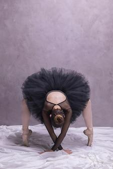 Bailarina de vista frontal, curvando-se em sapatos de ballet