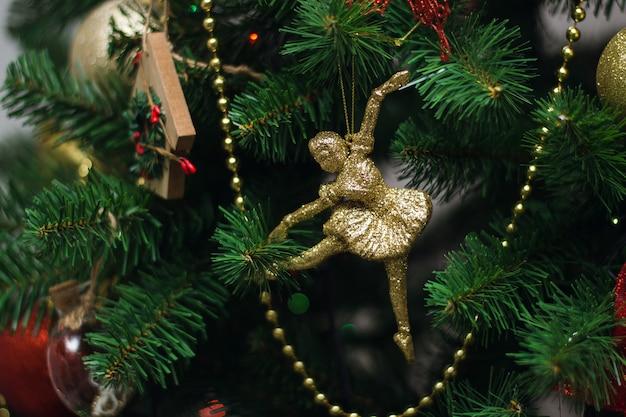 Bailarina dourada pendurada em uma árvore de natal. fundo de natal