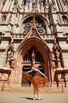 Bailarina elegante dançando em frente ao prédio antigo