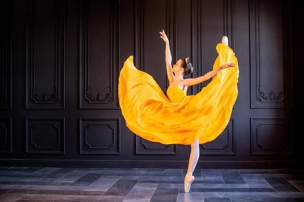 Bailarina elegante em sapatilhas de ponta dançando em uma longa saia amarela