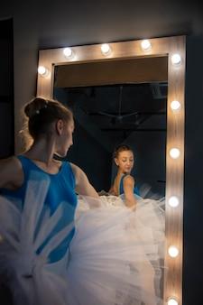 Bailarina elegante em vestido branco dançando no estúdio