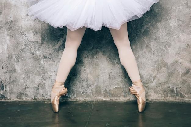 Bailarina elegante vestido branco dançando contra parede rústica