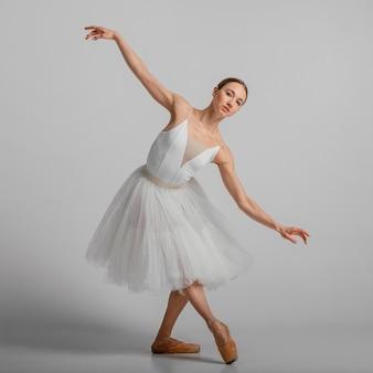 Bailarina em cena completa posando com sapatilhas de ponta