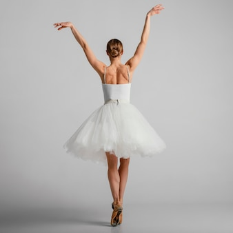 Bailarina em pé com sapatilhas de ponta, foto completa