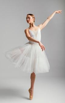 Bailarina em pé com sapatilhas de ponta, tiro completo