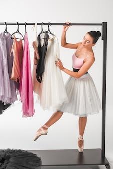 Bailarina em pé na ponta dos pés, escolhendo o tutu de cabides contra o pano de fundo branco