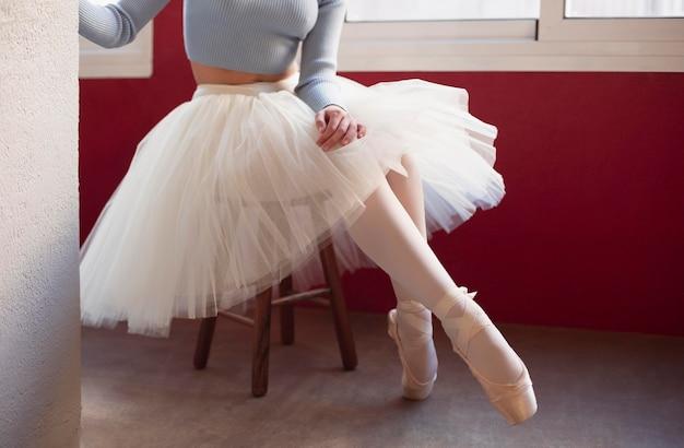 Bailarina em saia tutu ao lado da janela