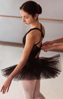 Bailarina em saia tutu se preparando para uma apresentação