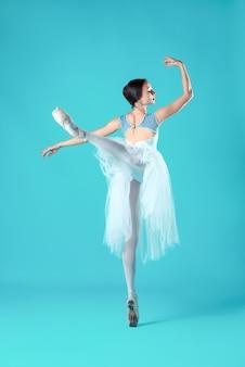Bailarina em vestido branco, posando nos dedos dos pés
