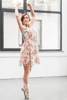 Bailarina em vestido floral posando em sapatilhas de ponta