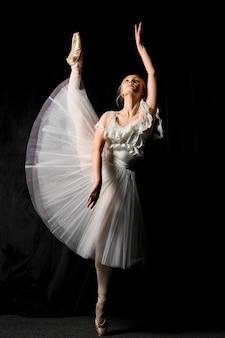 Bailarina em vestido tutu, posando com a perna para cima