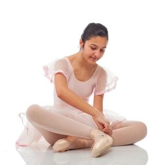 Bailarina, enquanto amarrando os sapatos para dançar.