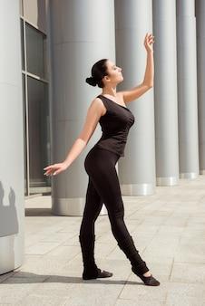 Bailarina esguia e graciosa dançando no prédio