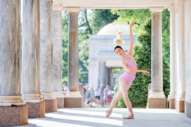 Bailarina esguia em sapatilhas de ponta e usando fantasia de silhueta dançando no contexto de uma arquitetura antiga no parque