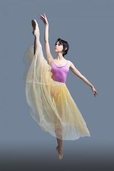 Bailarina está dançando em um cinza