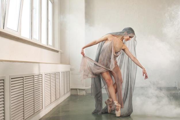 Bailarina está dançando em um vestido longo e sua cabeça está coberta com um véu cinza, com fumaça ao fundo