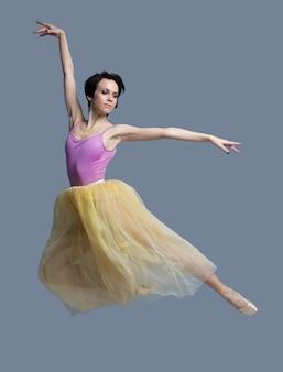 Bailarina está dançando no estúdio em cinza
