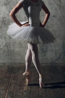 Bailarina fêmea. dançarina de balé jovem bonita, vestida com roupa profissional, sapatilhas e tutu branco.