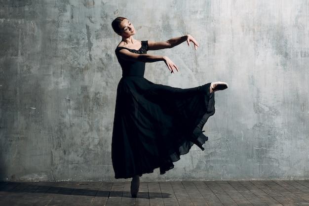 Bailarina fêmea. dançarina de balé jovem bonita, vestida com roupa profissional, sapatilhas e vestido preto.