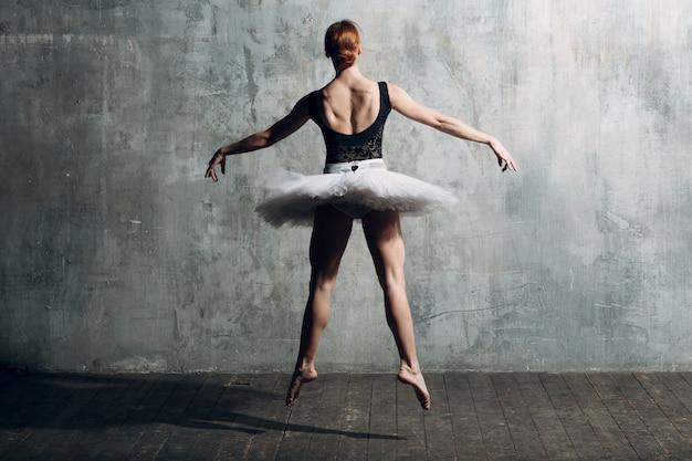 Bailarina fêmea. dançarina de balé jovem bonita, vestida com roupa profissional, sapatilhas, tutu preto e branco superior.