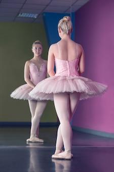 Bailarina graciosa de pé na primeira posição na frente do espelho