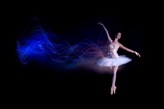Bailarina jovem com dança solo de tutu, fazendo o suporte nos dedos dos pés e deixa a fuga de vazamento de luz azul da silhueta em cena preta com piso refletindo
