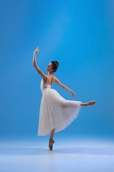 Bailarina jovem e graciosa em um vestido branco isolada em uma parede azul
