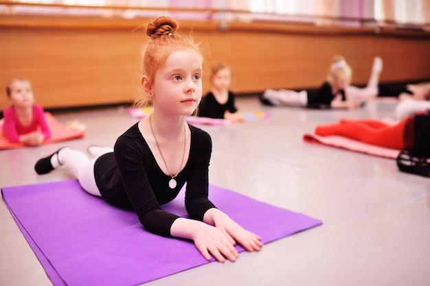 Bailarina linda garota ruiva, esticando e fazendo as divisões