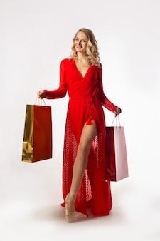 Bailarina linda jovem em um vestido vermelho com pacotes nas mãos em um fundo branco