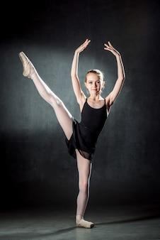 Bailarina. menina bonitinha posando e dançando no estúdio. a menina está estudando balé.