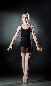 Bailarina. menina bonitinha posando e dançando no estúdio. uma pequena dançarina. fundo escuro. vestido preto.