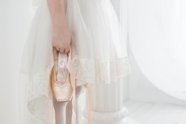 Bailarina menina em um lindo vestido branco segurando sapatilhas