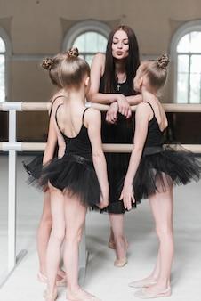 Bailarina meninas olhando para o treinador feminino fazendo beicinho perto da barra