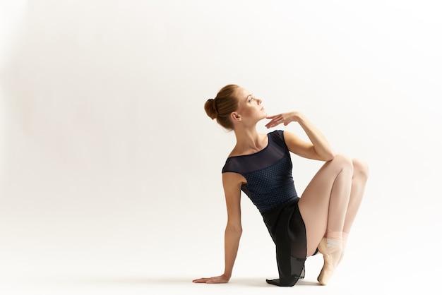 Bailarina mulher está esticando no estúdio
