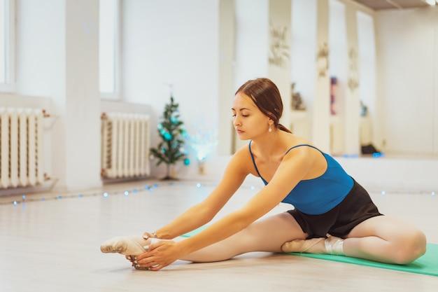 Bailarina na esteira na academia fazendo alongamento