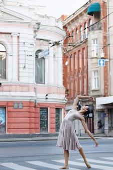 Bailarina na estrada na cidade na faixa de pedestres