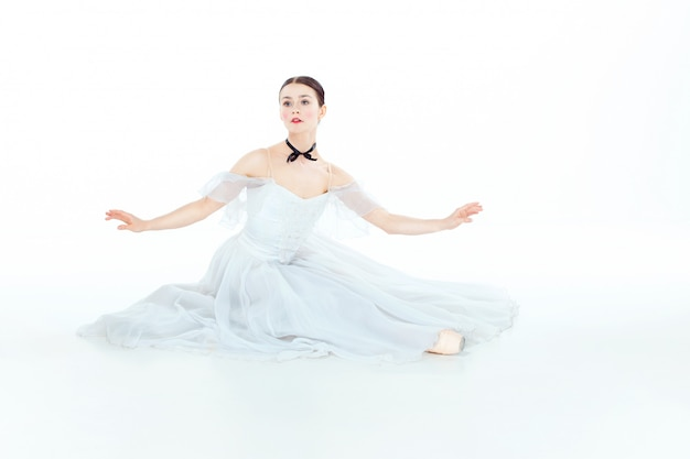 Bailarina no vestido branco que senta-se, estúdio.