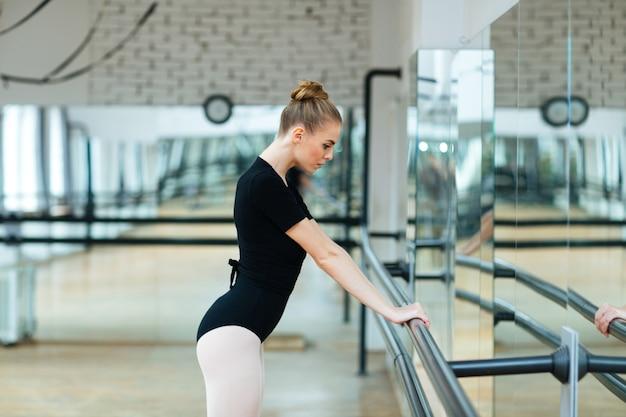 Bailarina pensativa em pé na aula de balé