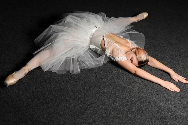 Bailarina posando ao fazer uma divisão no vestido tutu