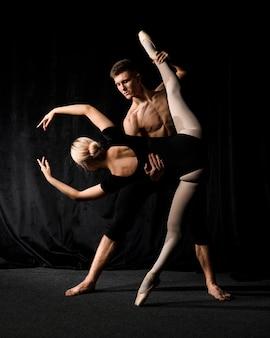 Bailarina posando com homem segurando a perna dela