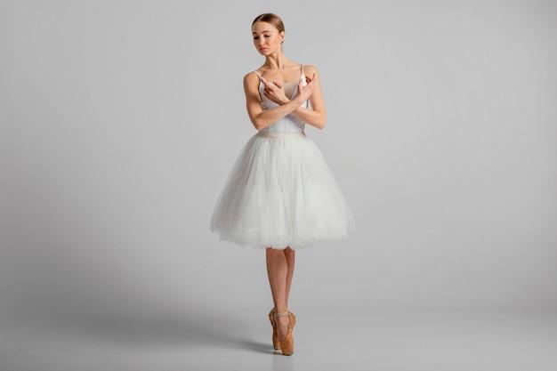 Bailarina posando com sapatilhas de ponta, foto completa