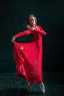 Bailarina posando em sapatilhas no pavilhão de madeira preto