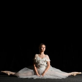 Bailarina posando em vestido tutu e fazendo uma divisão