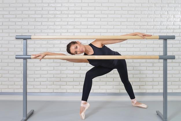 Bailarina posando perto de barre no estúdio de balé, retrato de corpo inteiro de dançarina de mulher bonita