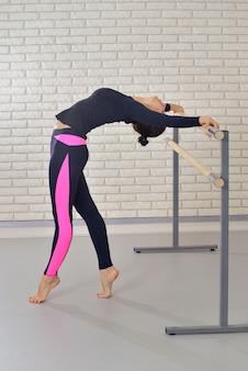 Bailarina praticando balé no estúdio de dança perto de barre, exercício de ponte