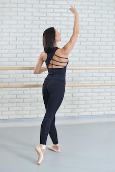Bailarina praticando balé no estúdio de dança perto de barre.