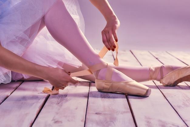 Bailarina profissional, calçar seus sapatos de balé.