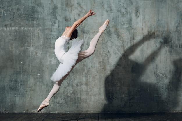 Bailarina pulando. dançarina de balé jovem bonita, vestida com roupa profissional, sapatilhas e tutu branco.