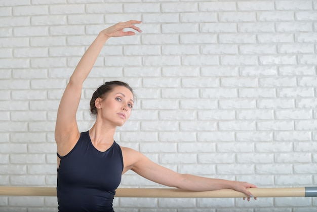 Bailarina que dança no estúdio do bailado perto da barra, retrato do close up.